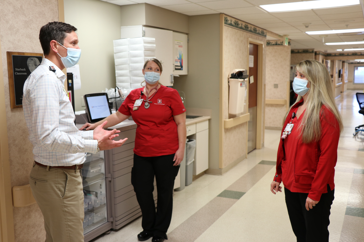 Healthcare workers converse in the hallway