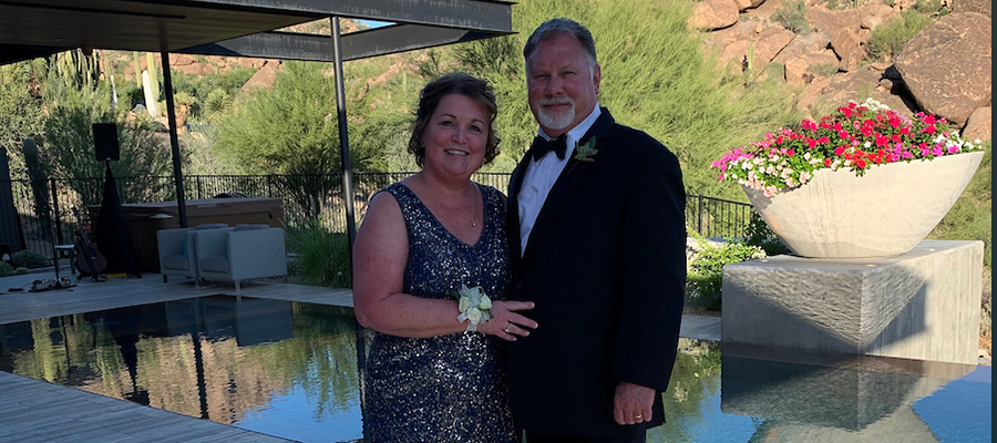 Christine and Warren dressed up and standing in front of a pool
