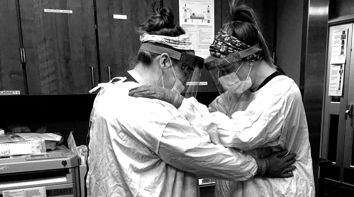 Healthcare workers embrace each other