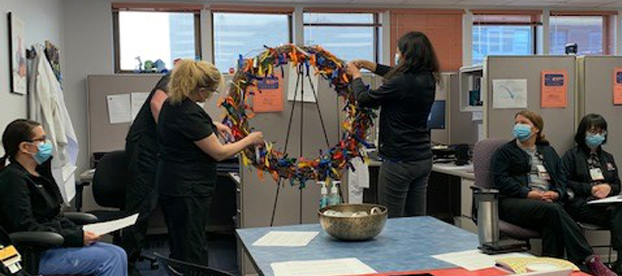 IU Health social worker Tina Stachmus ties the pink ribbon to the wreath